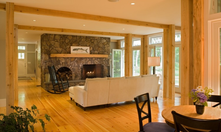 Focused on a 10 foot wide natural stone fireplace, the 20' by 22'  living room is open all around, to the entry hall and main stairway  at far left, to the open front porch and water view through French  doors at right, to the dining and screened porch in the right  foreground of this view.