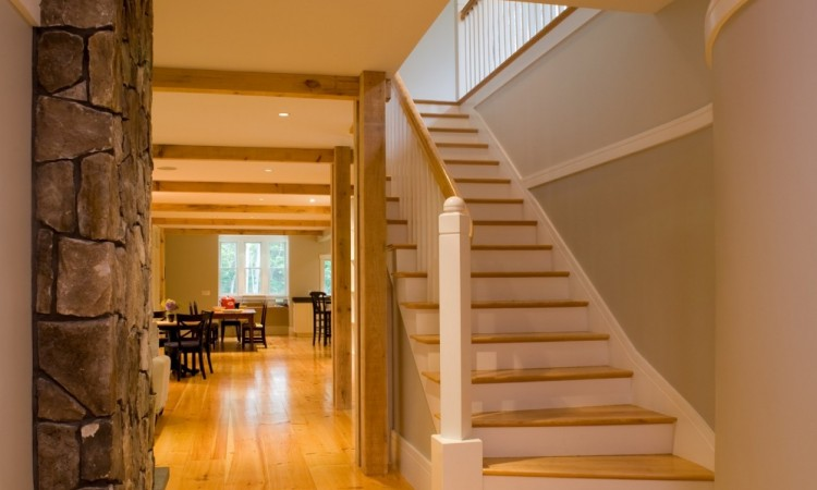 From the main entry hall, the entire 76 foot length of  the ground floor is visible, with dining area in the  distance.