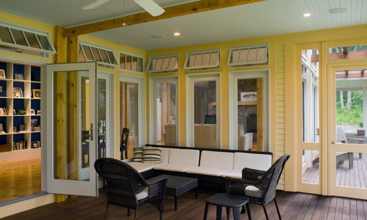 A portion of the screened porch with views and access to the dining and  kitchen at far left, living room at center, and outdoor porch at right.