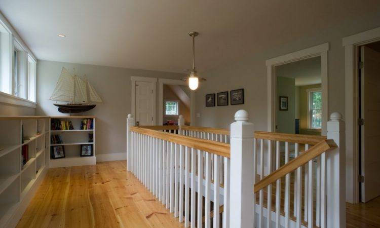 This open stair hall is the focal point of the second floor, with access to all bedrooms and plenty of open storage. At far left,  operable clerestory windows facing north provide a draft to  carry warm air rising from the first floor, completing the natural  chimney effect.