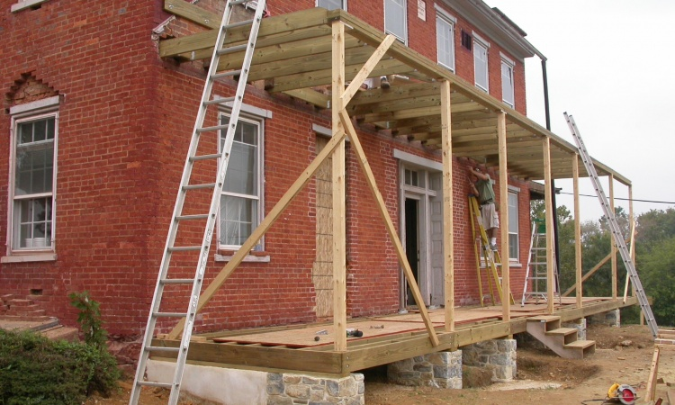 Original door and window openings were restored based on site evidence and careful analysis of historic photo-documentation, and the wraparound porch was completely rebuilt.